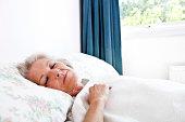 Senior woman sleeping in bedroom at home