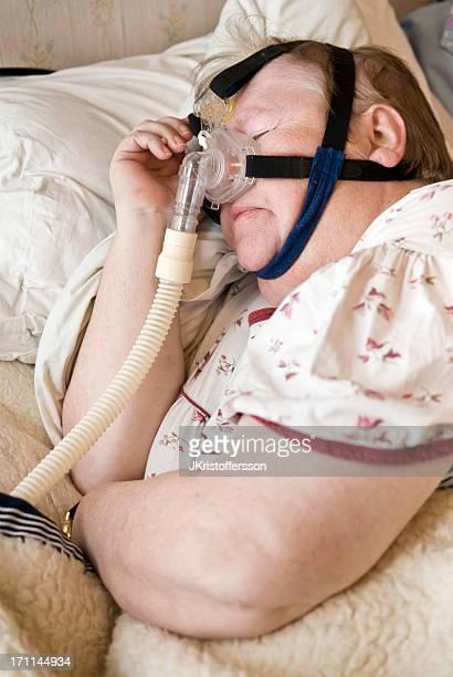 Donna anziana maschera con CPAP per apnea del sonno