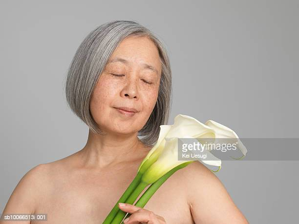 Senior woman smelling flowers, close-up