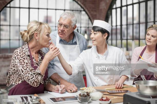 Senior woman smelling ingredient in cooking class