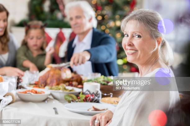 Senior vrouw glimlach voor de camera bij familie kerstdiner