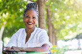 In a quiet park, a beautiful senior woman enjoys a peaceful moment and smiles at the camera.