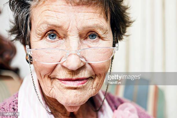 Senior woman smiles gently over her glasses at camera