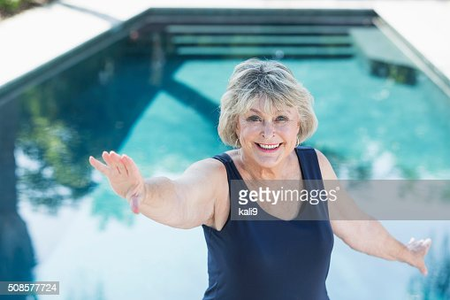 Senior woman smiling, exercising by swimming pool : Stock Photo