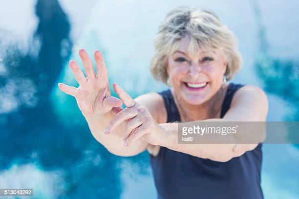 Senior woman smiling, exercising by swimming pool