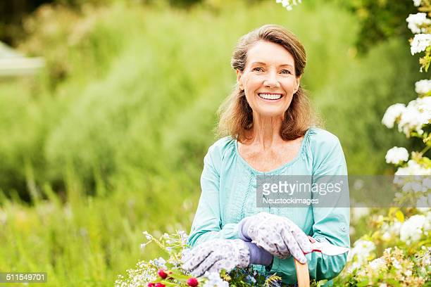Senior Woman Smiling While Holding Pruning Shears In Garden