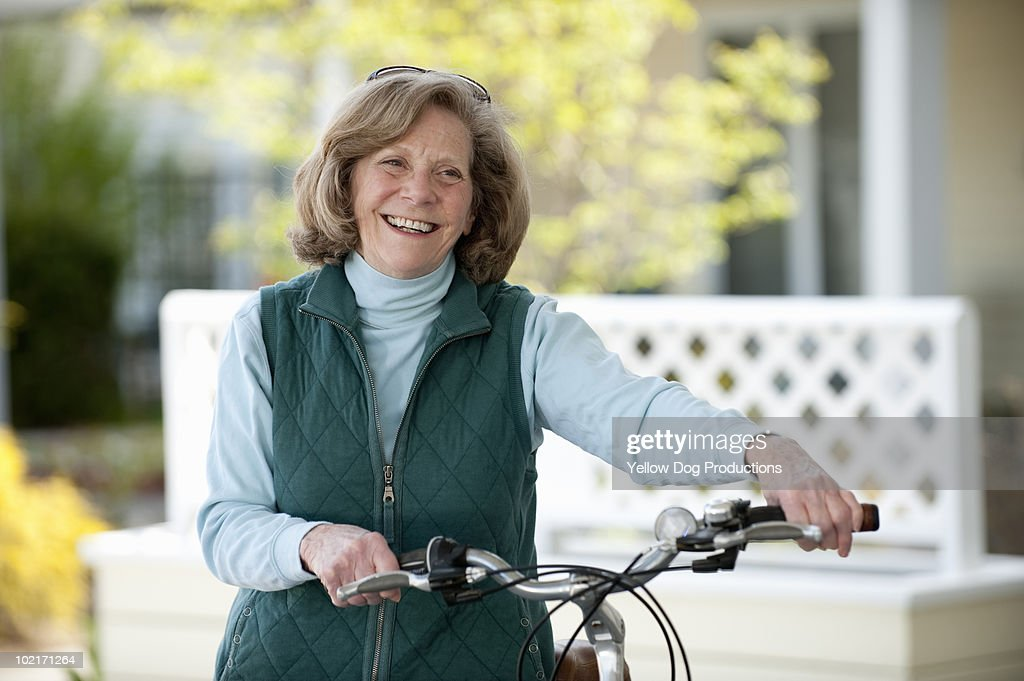 Senior woman smiling with bicycle
