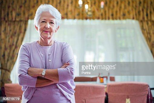 Senior woman standing arms crossed in nursing home
