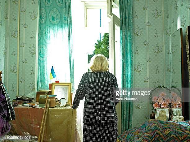 Senior woman standing at door, rear view