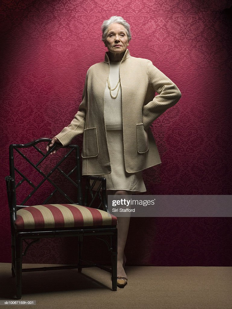 Senior woman standing by antique chair, portrait : Stock Photo
