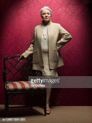 Senior woman standing by antique chair, portrait : Foto de stock