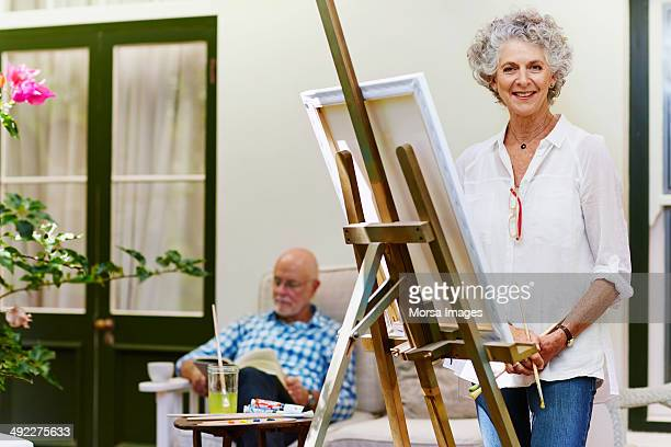 Senior woman standing by canvas at porch