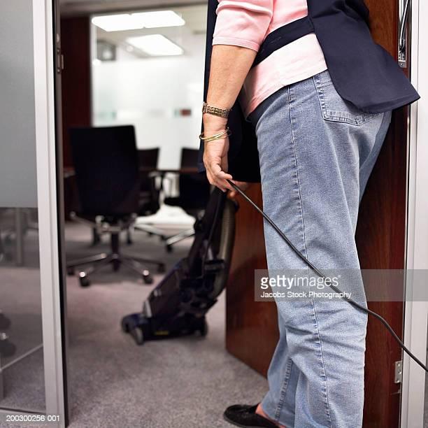 Senior woman standing in doorway hoovering office