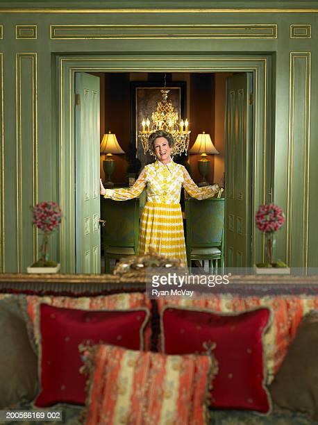 Senior woman standing in doorway, smiling, portrait
