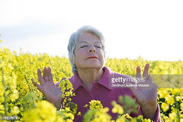 Senior woman standing in field of canola, eyes closed, hands up