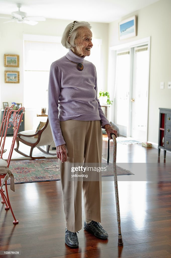 Senior woman standing in her living room : Stock Photo