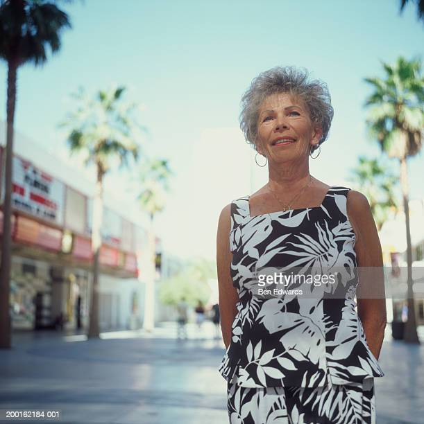 Senior woman standing in street, low angle view