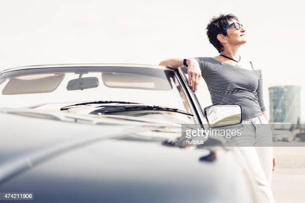 高齢者の女性の横に転換クラシックカー