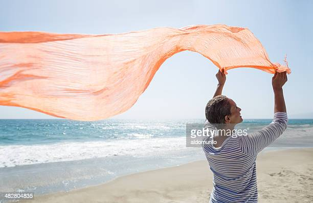 Senior woman standing on beach holding scarf