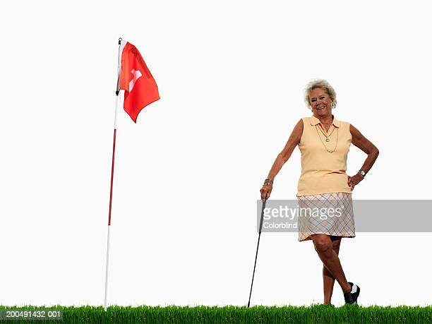 Senior woman standing on golf green, smiling, portrait