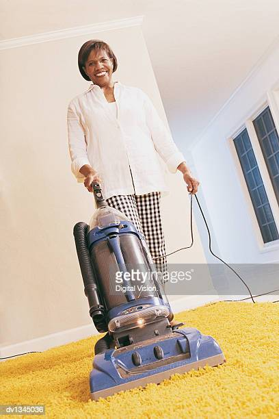 Senior Woman Standing on Her Carpet With a Vacuum Cleaner