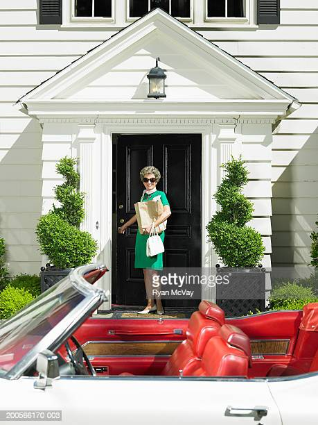 Senior woman standing on porch, convertible car in foreground