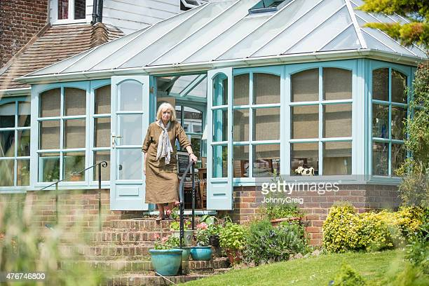 Senior woman standing on the steps of her conservatory