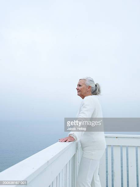 Senior woman standing on wooden terrace, looking out to sea, side view