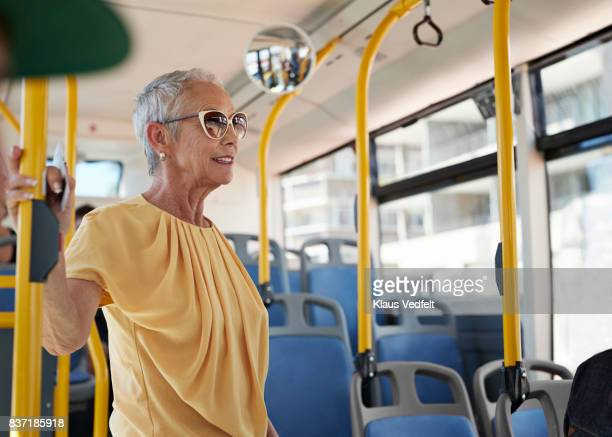Senior woman standing up, in public bus
