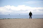 Senior woman standing, watching ocean