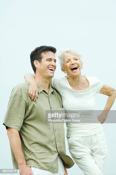 Senior woman standing with arm around adult son's shoulder, both smiling