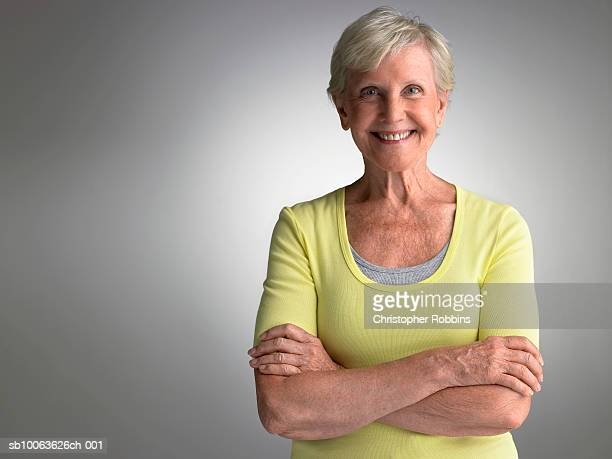 Senior woman standing with arms crossed, smiling, portrait