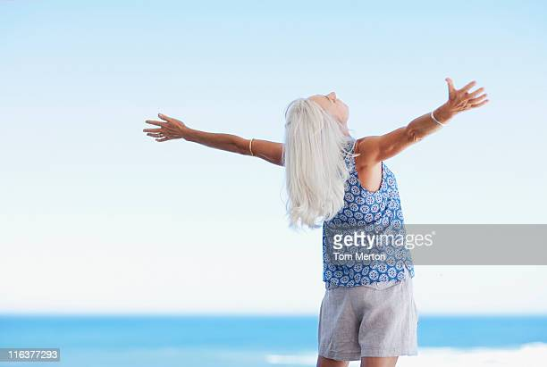 Senior woman standing with arms outstretched on beach
