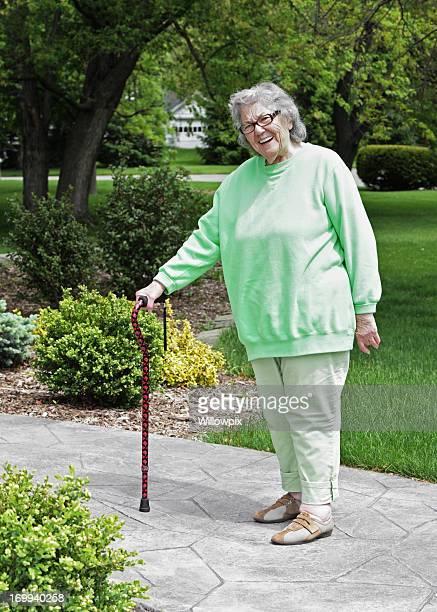 Senior donna in piedi con un bastone