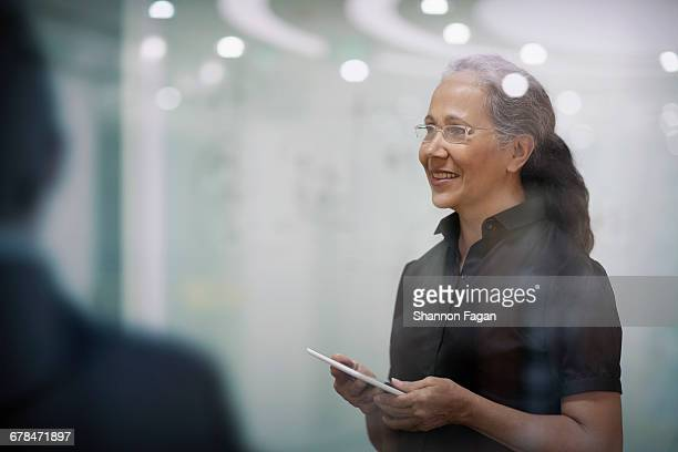 Senior woman standing with smart tablet computer