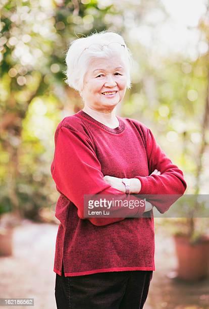 Senior woman stands in the garden