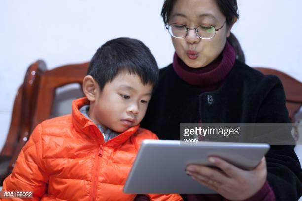 Senior woman storytelling with boy using digital tablet