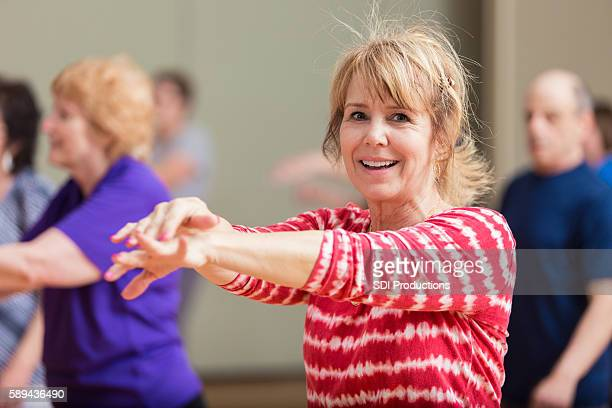 Senior woman stretches in exercise class