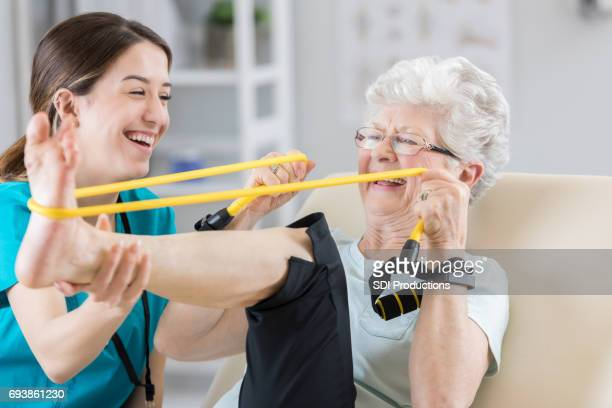 Senior woman stretches leg with resistance band