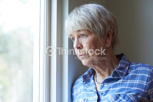 Senior Woman Suffering From Depression Looking Out Of Window : Stock Photo