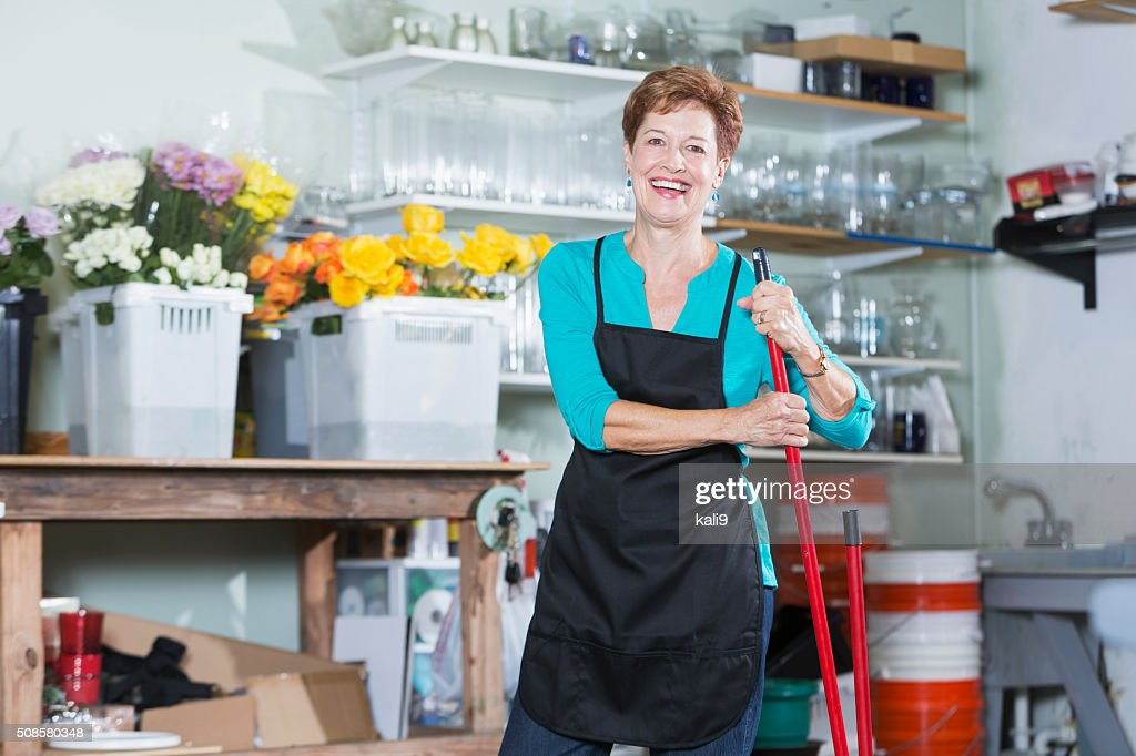 Senior woman sweeping floor of flower shop : Stock Photo