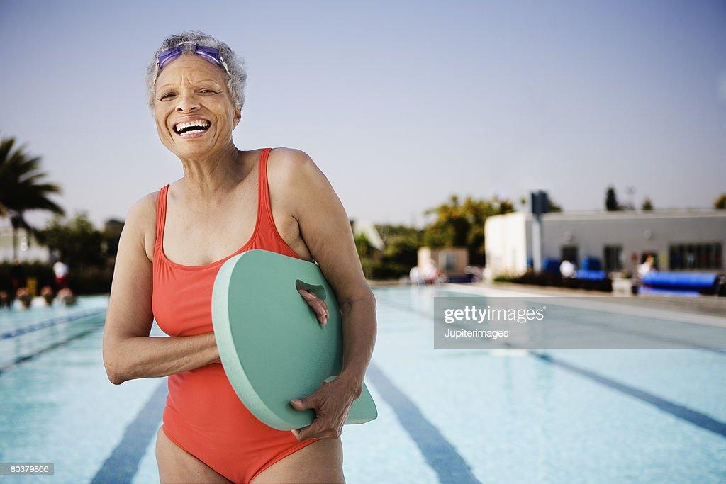 Senior woman swimmer holding kickboard : Stock Photo
