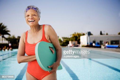 Senior woman swimmer holding kickboard