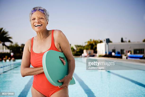 Senior woman swimmer holding kickboard