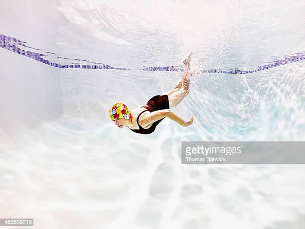 Senior woman swimming underwater in pool