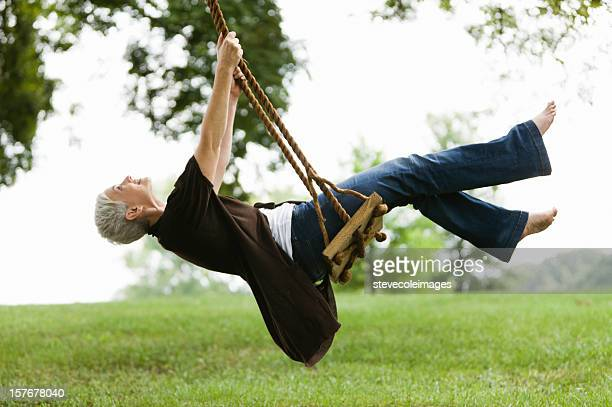 Senior Woman Swinging Under a Tree