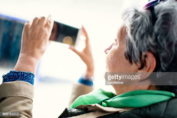 Senior woman taking a photo by smartphone