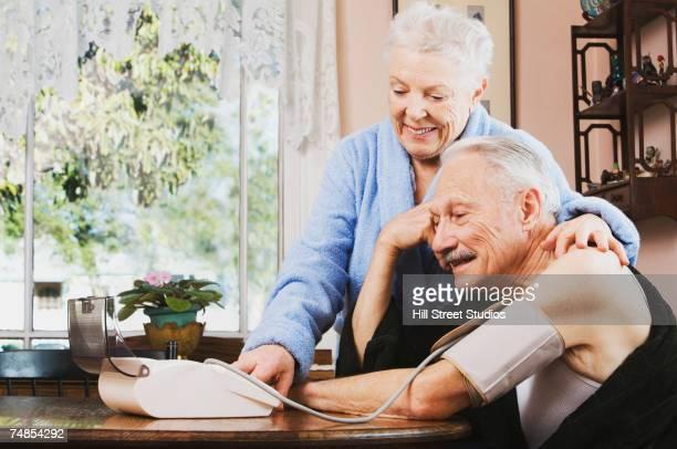 Senior woman taking husband's blood pressure