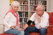 Senior woman taking man's blood pressure