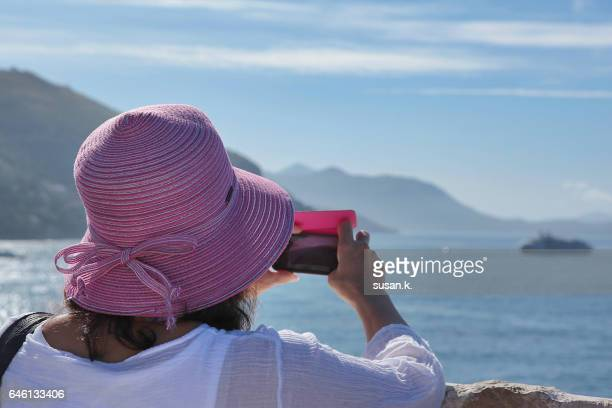 Senior woman taking picture of sea view with mobile phone